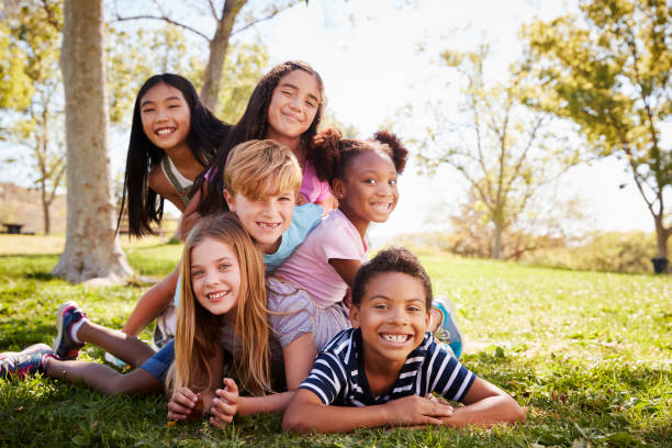Multi-ethnic group of kids lying on each other in a park